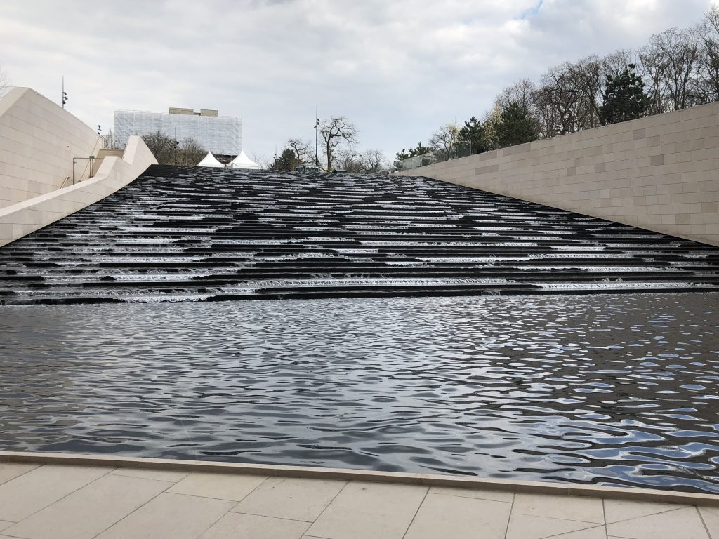 An outside waterfall cascades via steps into a basin outside the auditorium of the Louis Vuitton Foundation building.