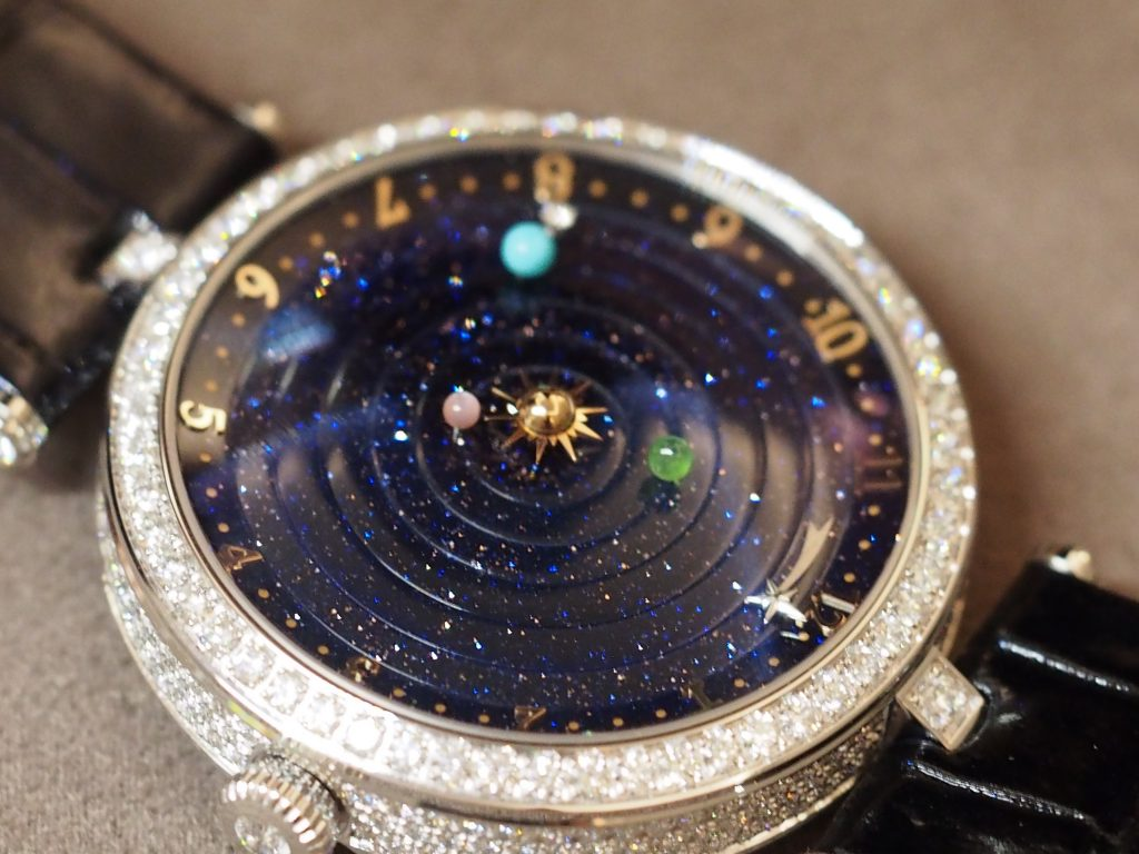 The case and bezel of the Van Cleef & Arpels Lady Arpels Planetarium watch is set with diamonds.