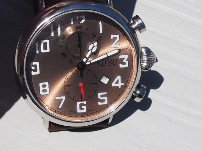 The bronze dial with luminous hands and large numbers is easy to read