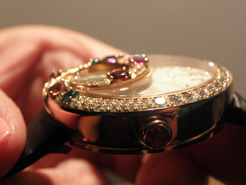 The tourbillon cage is outlined in a 3D swirl of gold and gemstones