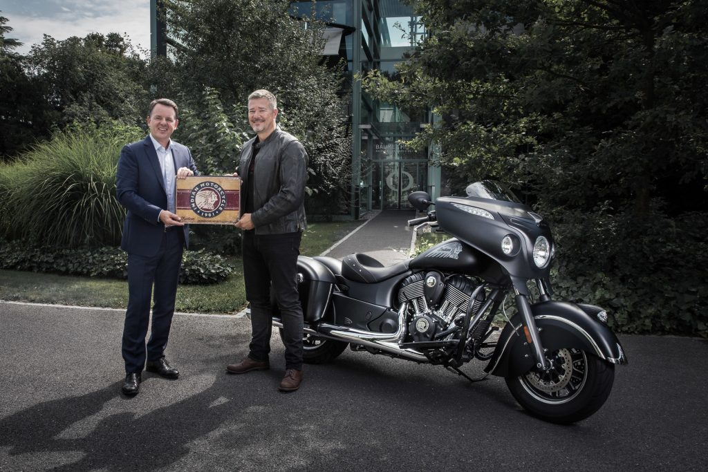 Alain Zimmermann, CEO of Baume & Mercier, with Grant Bester,Vice President, Indian Motorcycle EMEA, celebrate their partnership in front of a Chieftain Dark Horse® motorbike.