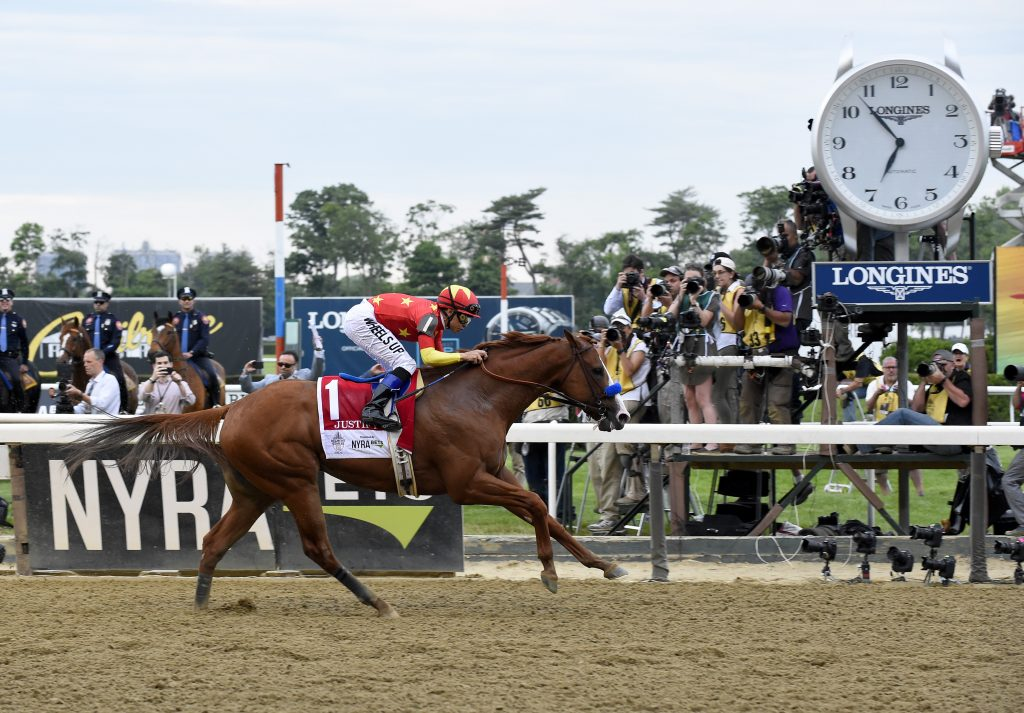 Justify, ridden by Mike Smith, wins the Triple Crown and the 150th running of the Belmont Stakes, Saturday, June 9, 2018, at Belmont Park in Elmont, NY. Longines, the Swiss watchmaker known for its elegant timepieces, is the Official Timekeeper and Watch of the 150th running of the Belmont Stakes. (Photo by Diane Bondareff/AP Images for Longines)