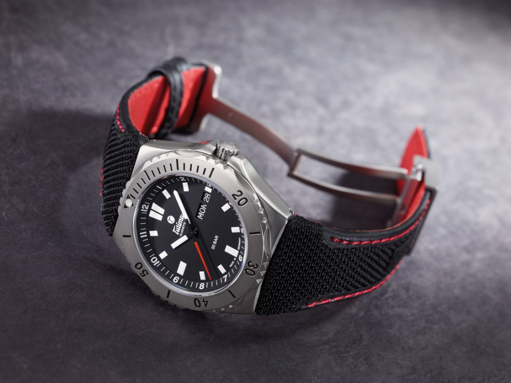 The black-dialed Seven Seas features a black Kevlar strap with red stitching and red inner lining
