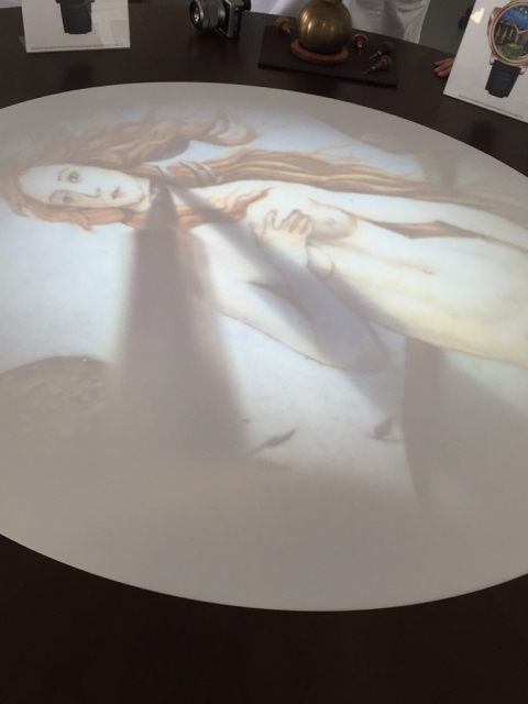 As the artists are hand painting the dial, the image is live-streamed onto a table in the center of the room.