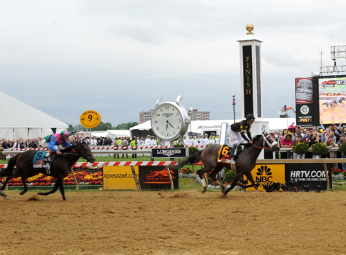 Oxbow races by the Longines clockat the finish line of the 138th running of the Preakness STaesk yesterday. (photo: Diane Bondareff/Invision for Longines/AP Images)