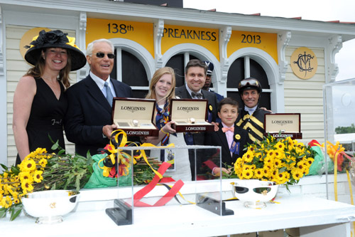 Juan Carlos-Capelli, center, with his son Thomas, and Jennifer Judkins, left, both of Longines, award trainer D. Wayne Lukas, second left, jockey Gary Stevens and Erin Kelley, daughter of owner Brad Kelley, with their Longines St. Imier chronographs after their horse Oxbow won the 138th Preakness Stakes, May 18, 2013, in Baltimore, MD.  (Diane Bondareff/Invision for Longines/AP Images)
