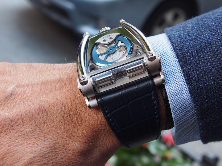 The watch features a roll-bar like protective support of the sapphire, titanium and gold case.
