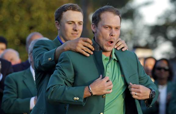 Willett donning the Green Jacket (being helped by Spieth). Photo courtesy of Christ Carlson/AP