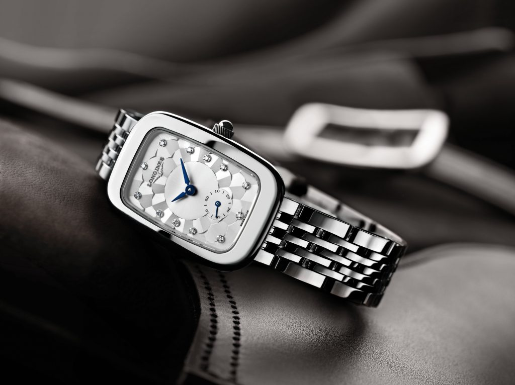 "in the shape of its stainless-steel case, this Longines Equestrian timepiece features a silver-coloured ""damier"" dial enhanced by blued-steel hands and adorned with diamond indexes. The polished stainless-steel case and bracelet are further enhanced by the 60 Wesselton VVS diamonds, for a total of 0.504 carats, surrounding its bezel."