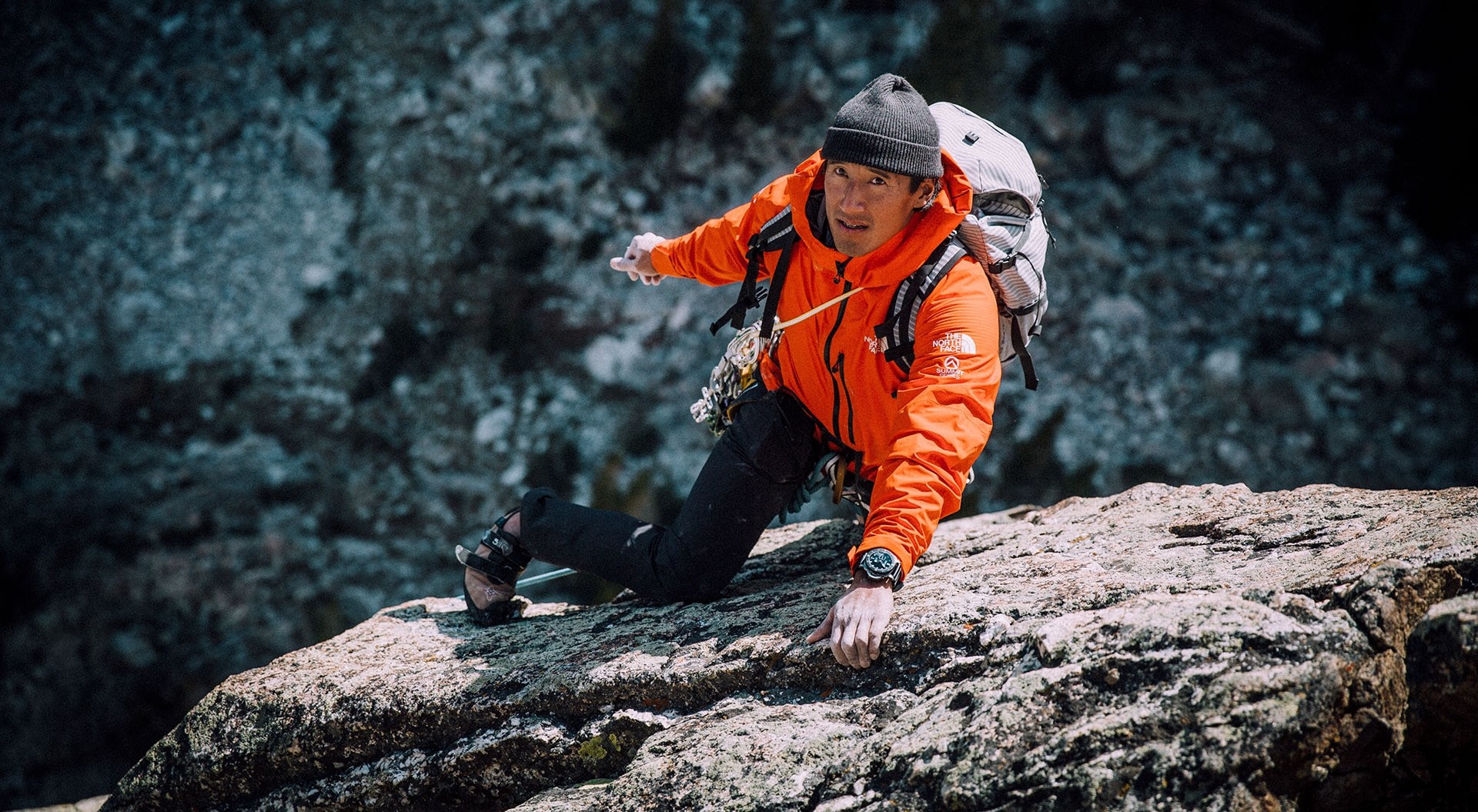 """Panerai Unveils Submersible Chono Flyback Watches in Collaboration With Jimmy Chin Officine Panerai, the Swiss watch brand with rich Italian roots, is a master at leading the way when it comes to adventure watches. This brand has been crafting dive watches and sport watches for nearly a century and has even supplied certain armed forces with underwater watches for decades. A few years ago, the brand launched an exciting new aspect with specific watches: adventure experiences. As Panerai partnered with adventurers and explorers around the world, it began offering limited-edition watches to collectors that came with a paired """"experience."""" The most recent: Jimmy Chin. Mountaineer, alpinist climber, photographer and film maker, adventurer Jimmy Chin lives life on the edge – literally. He has climbed extreme mountains (including Everest, the summit of which he also skied off of), survived multiple avalanches and won an Academy Award (for co-directing the documentary Free Solo). The multi-talented explorer is a Panerai brand ambassador and recently helped design a watch in his name. The Panerai Submersible Chrono Flyback Jimmy Chin Xperience edition watch was created in a limited edition of just 14 pieces and was sold with an accompanying multi-day event in his hometown of Jackson Hole, Wyoming. There, proud owners of the watch spent a couple of days climbing the Grand Tetons with Chin, learning to wake surf in Jackson lake, and experiencing Chin's favorite restaurants. Panerai has had several similar experiences with its different ambassadors and their special timepieces over the past year or so, but this was the first event to be held in America. The Xperience watch is a light weight 47mm titanium piece with black matte DLC coating. The crown, lever and bezel are in titanium for nice contrast. The hands are filled with white Super-LumiNova and the dial is a shaded charcoal gray with blue accents. The case back features an etching of a dramatic mountainous landscape with"""