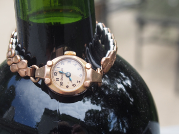 A mechanical 1940's Bulova (shown on the neck of a wine bottle to demonstrate its petite  size)
