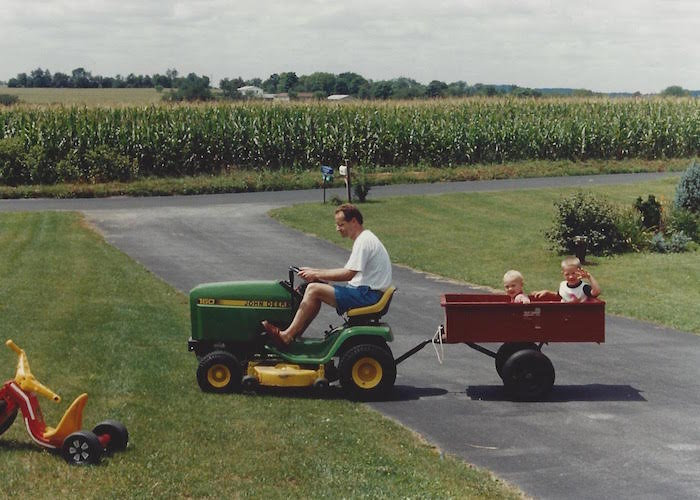 Dad driving me and my brother around in the tractor.